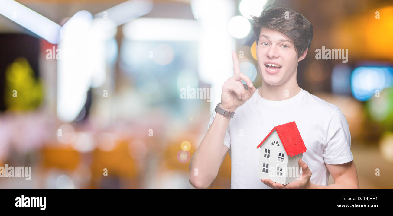 Young man holding house over isolated background surprised with an idea or question pointing finger with happy face, number one - Stock Image