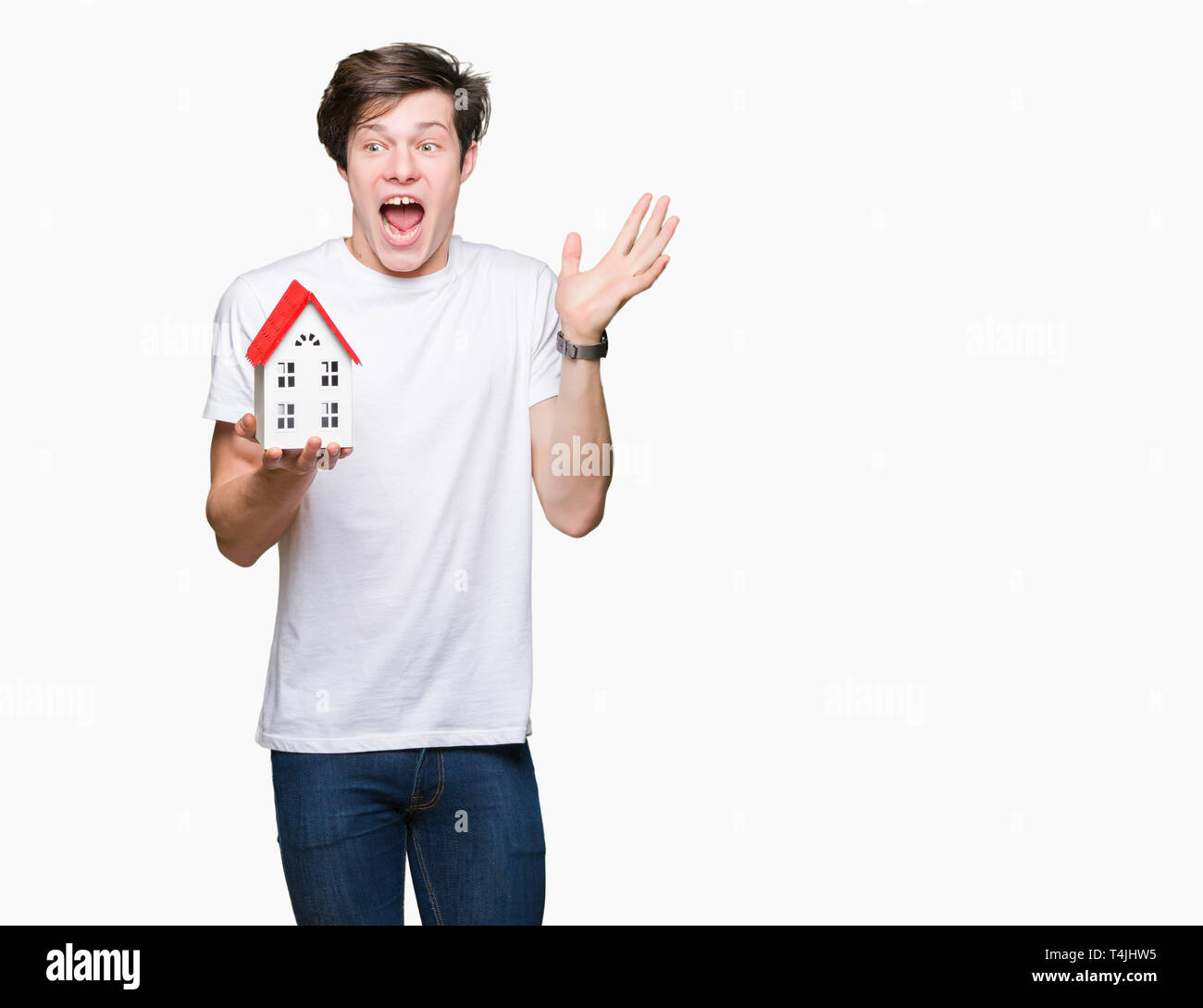 Young man holding house over isolated background very happy and excited, winner expression celebrating victory screaming with big smile and raised han - Stock Image