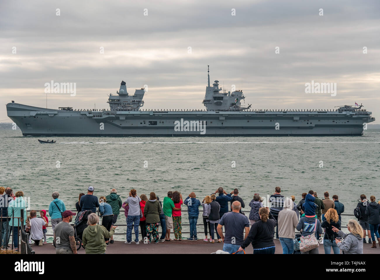 People line the sea wall at Southsea seafront, UK on 18/8/18 to watch the aircraft carrier HMS Queen Elizabeth leave for it's deployment to the USA. Stock Photo