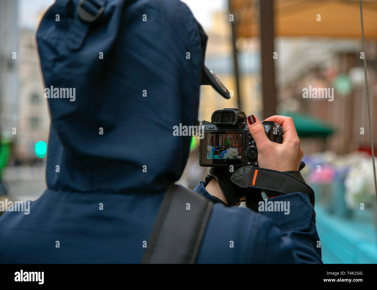 Girl-photographer takes photos of veranda outdoor cafe on the streets of the city.The photo was taken from the back, on the camera screen you can see - Stock Image