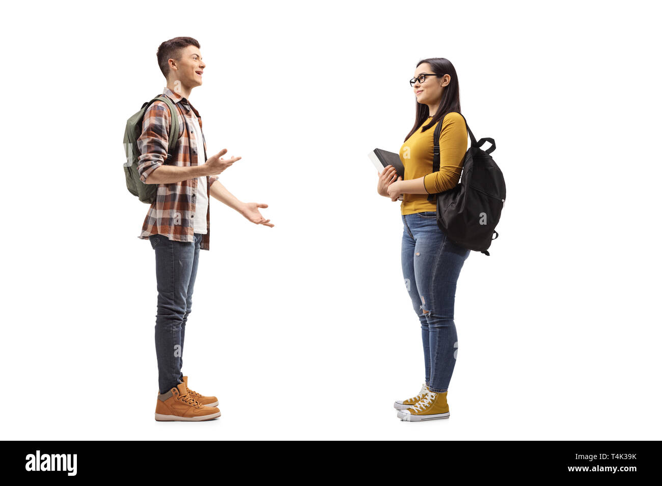 Full length profile shot of male and female students talking isolated on white background - Stock Image