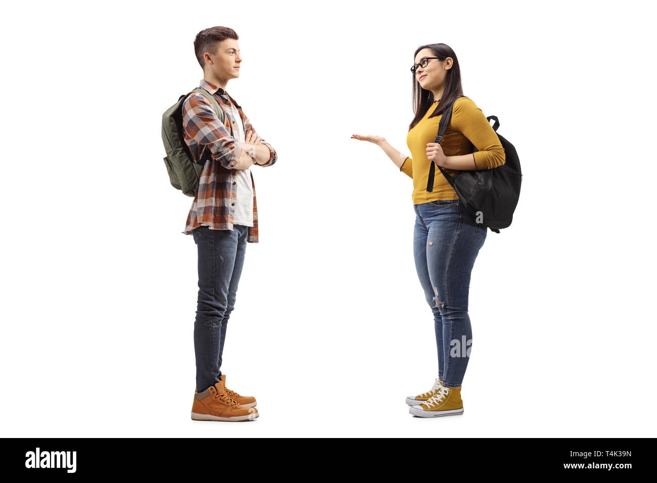 Full length profile shot of female student talking to a male student friend isolated on white background - Stock Image