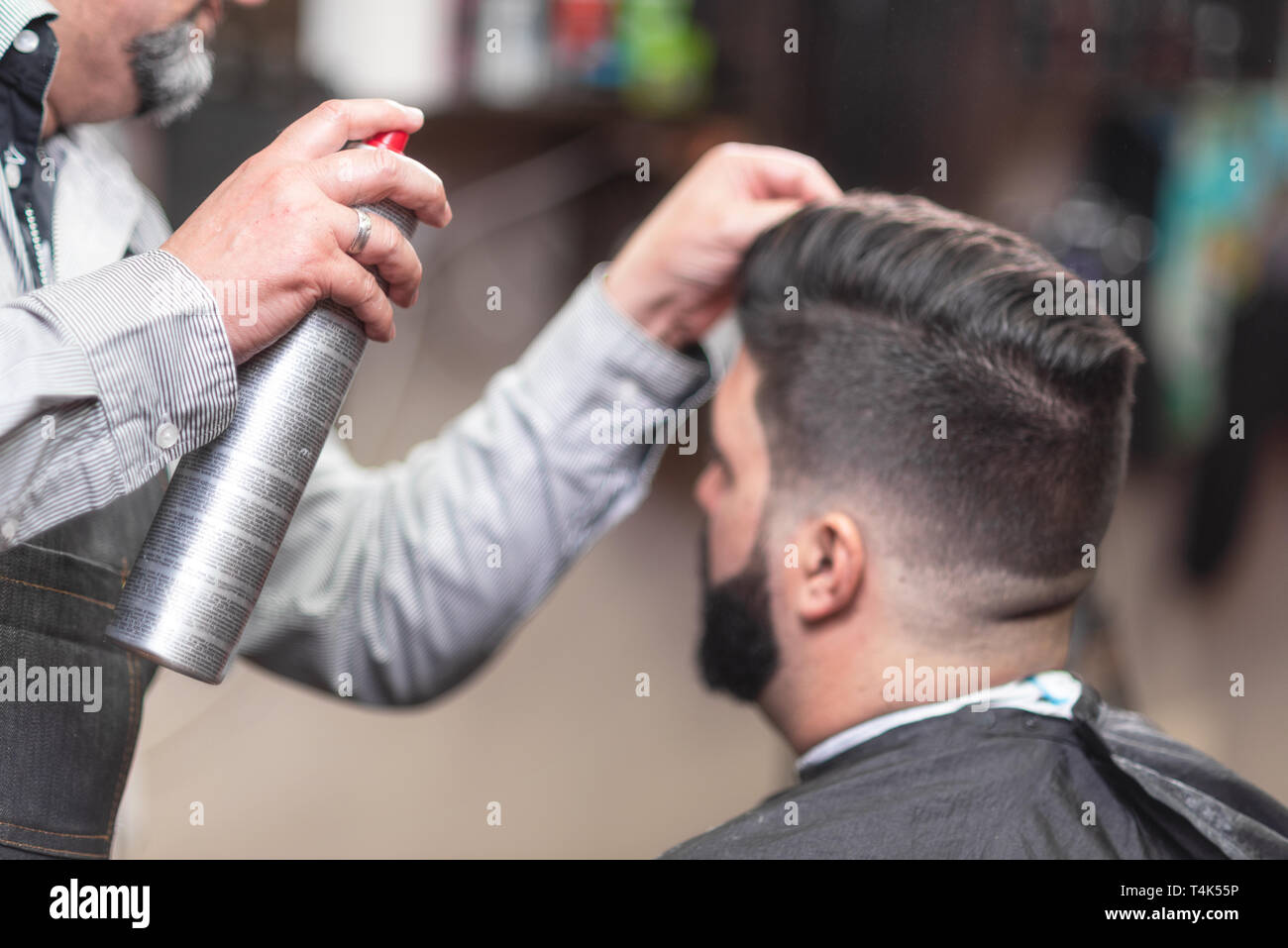 Master barber making modern hairstyle fixating hair with spray . - Stock Image