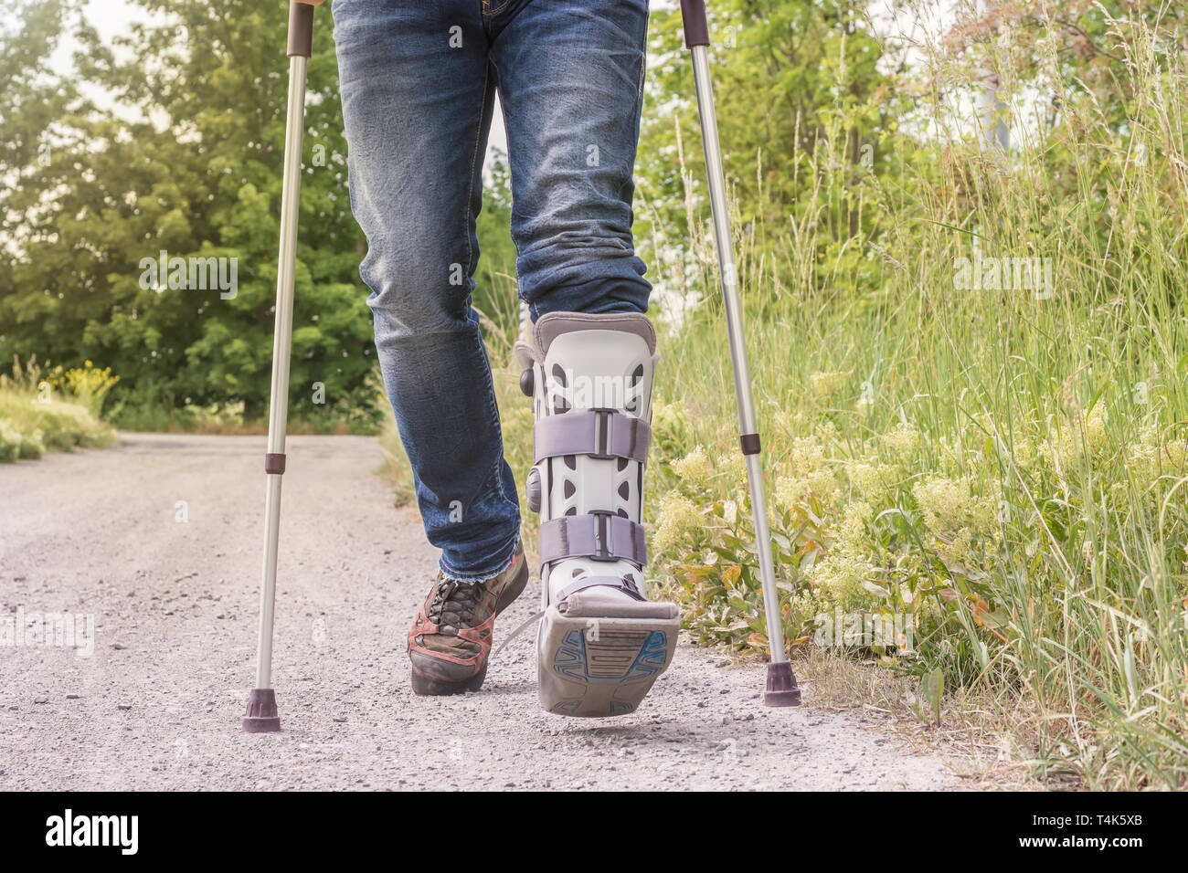 Man is running with an orthosis and walking aids on a dirt road - Stock Image