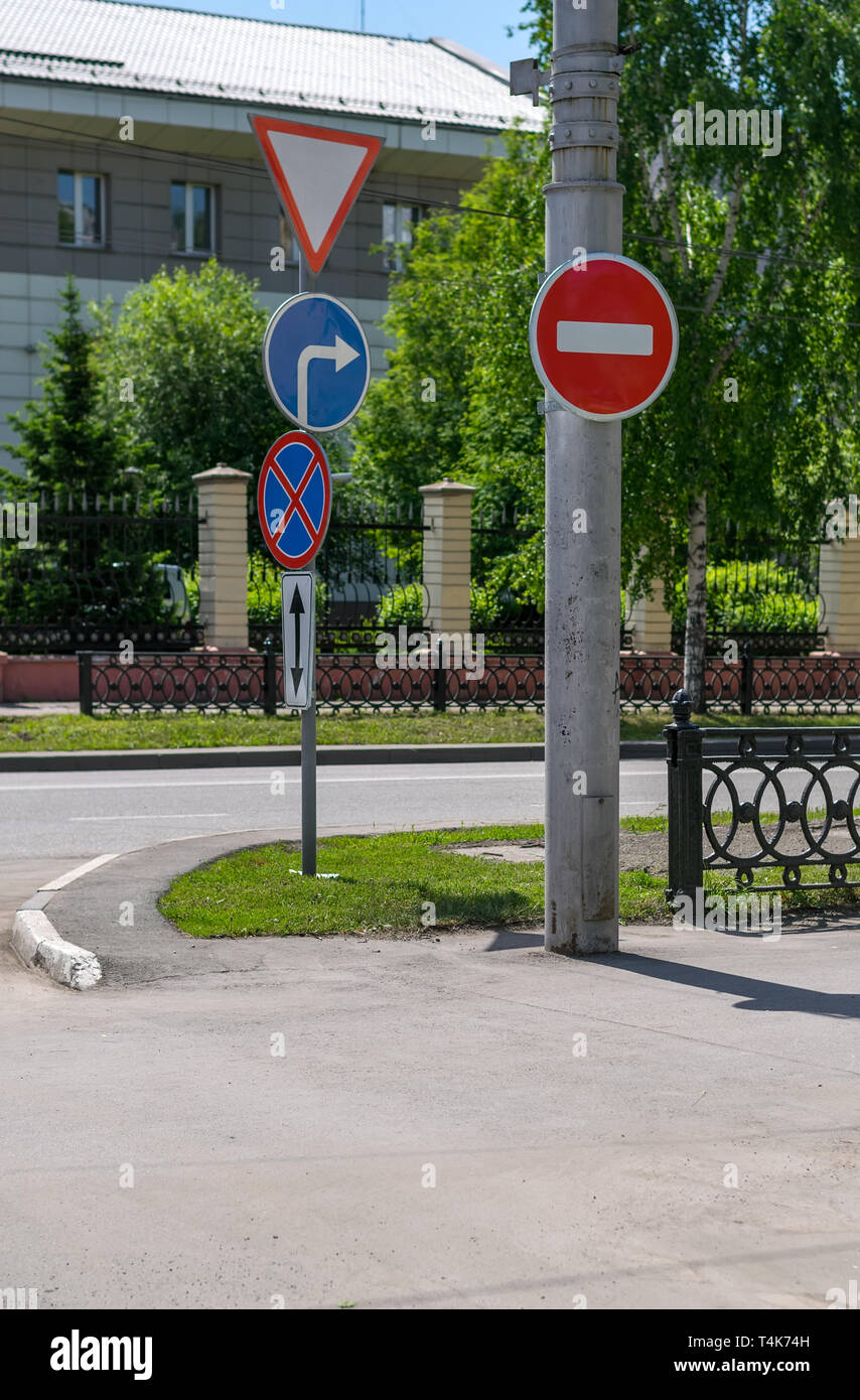 absurd, a contradiction of traffic signs on city streets. Errors of city symbols on the road - Stock Image