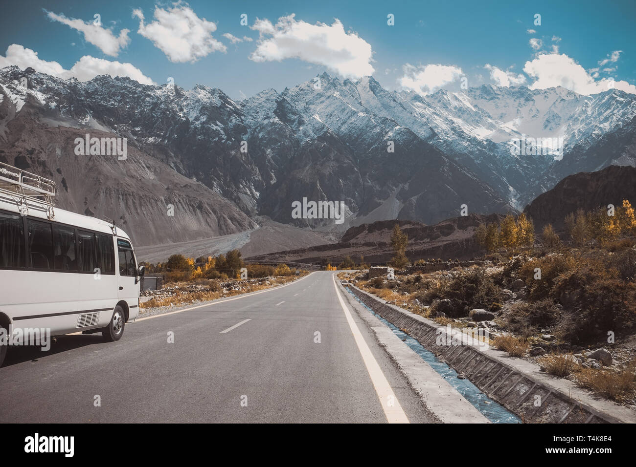 Paved road in Passu with a view of snow capped mountain range, Karakoram highway in Gojal Hunza. Gilgit Baltistan, Pakistan. Stock Photo