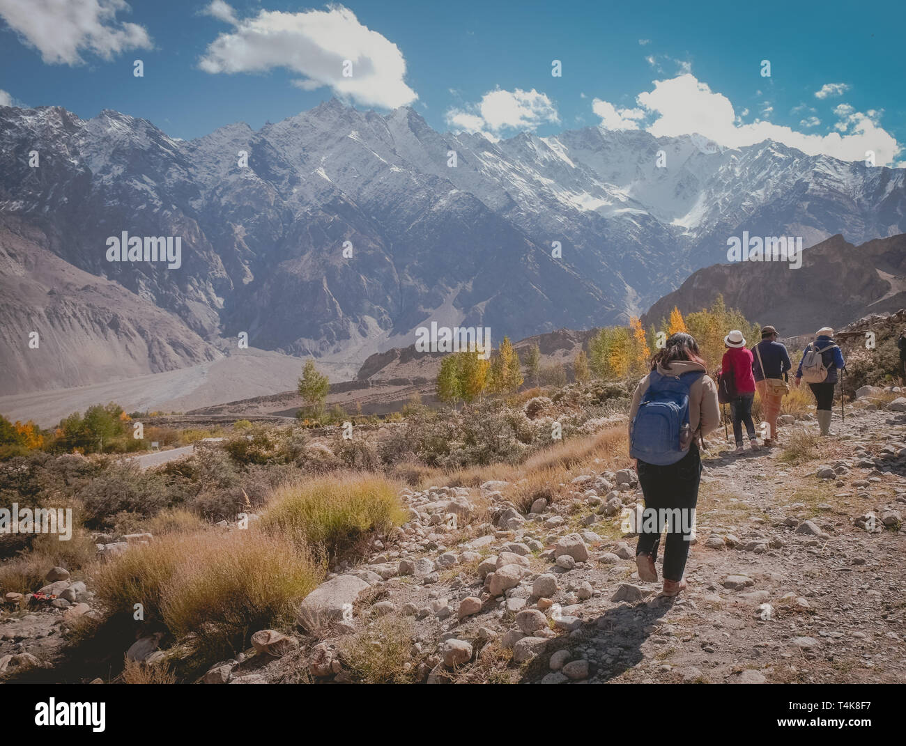 Tourists walking along the track in Passu trekking trail, surrounded by snow capped mountains in Karakoram range. Gilgit Baltistan, Pakistan. Stock Photo
