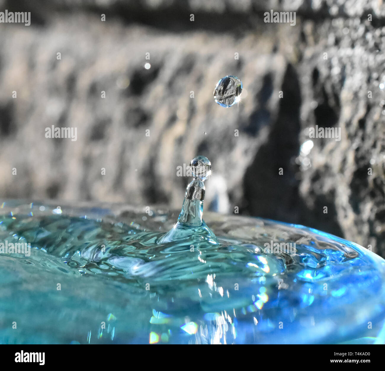 Water droplet formation showing reflections in the sun - Stock Image