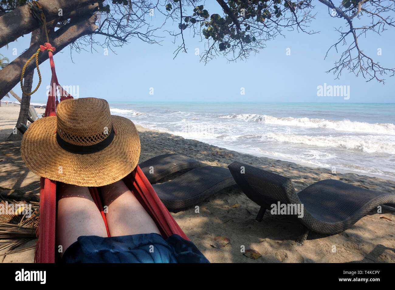 Sun Hat on the Feet of a Woman Relaxing in a Hammock with Ocean Views - Stock Image