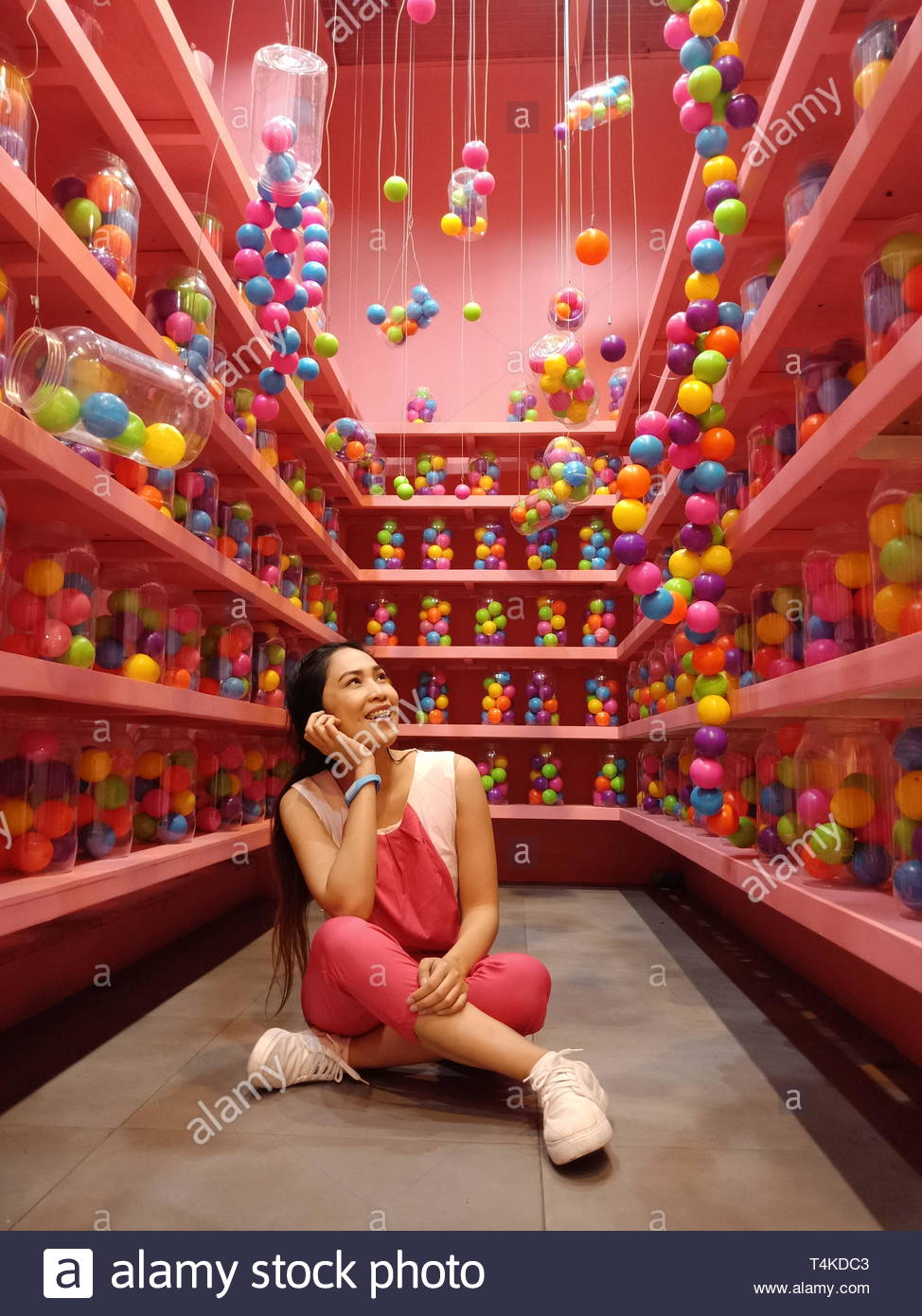 woman sitting in the middle of pink shelves - Stock Image