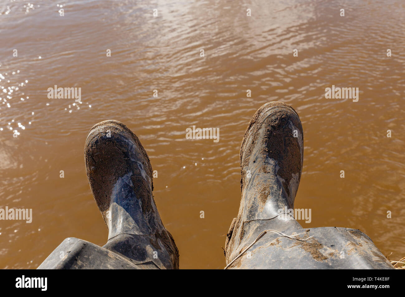 legs of a fisherman sitting in dirty rubber boots on the bank of the river with dirty water in the background - Stock Image