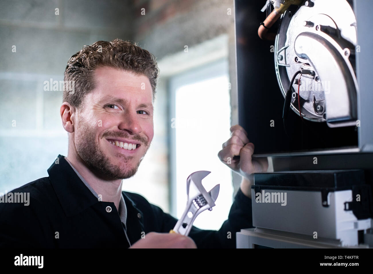 Portrait Of Male Heating Engineer With Adjustable Wrench Servicing Boiler - Stock Image
