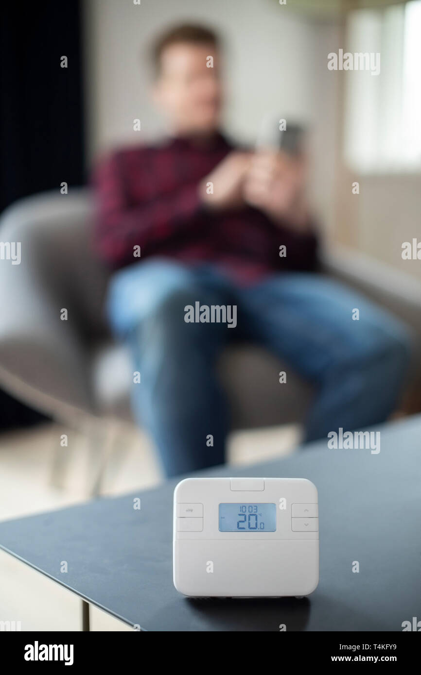 Man Controlling Central Heating Smart Meter Using App On Mobile Phone - Stock Image