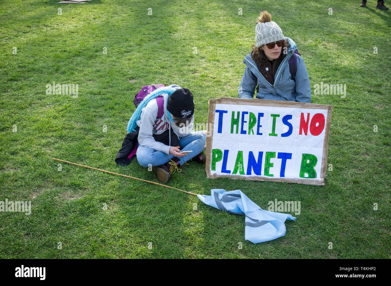 "A mother and child sit on the grass with a 'There is no Planet B"" banner on Parliament Green, Westminster for the Extinction Rebellion demonstration Stock Photo"