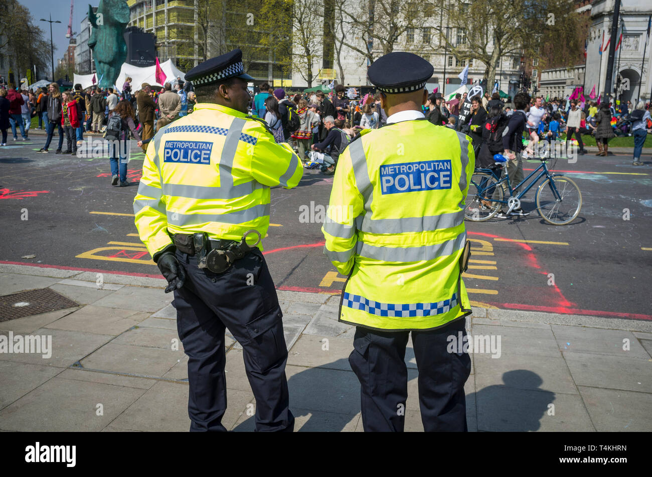 Two Metropolitan Policemen watch the Extinction Rebellion demonstration at Marble Arch - Stock Image