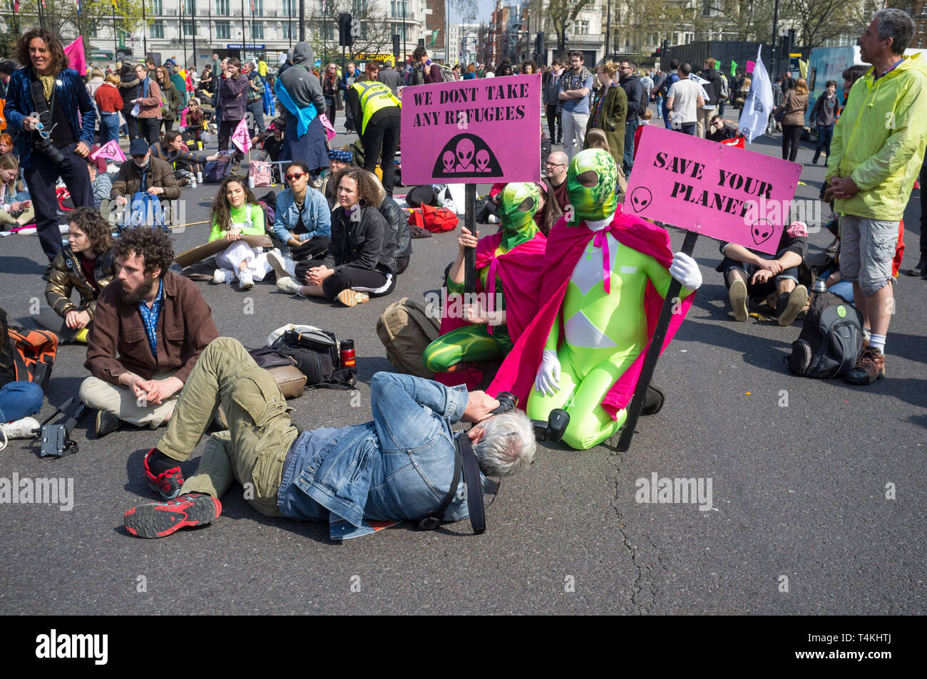 Two demostratos dressed as aliens are photographed at the Extinction Rebellion demonstration in Marble Arch - Stock Image
