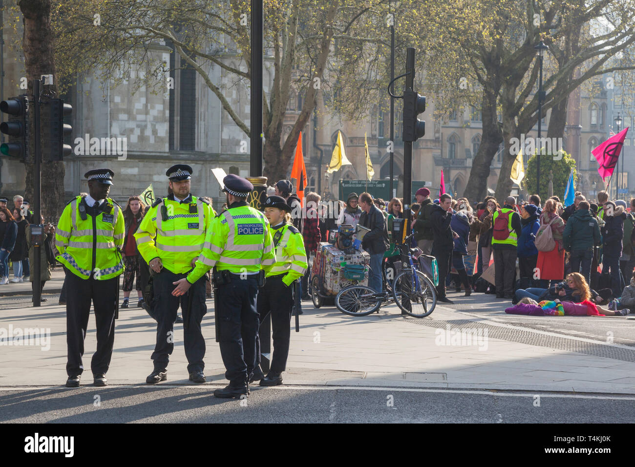 Metropolitan Police stand by on Parliament Square, Westminster for the Extinction Rebellion demonstration with protestors and banners behind - Stock Image