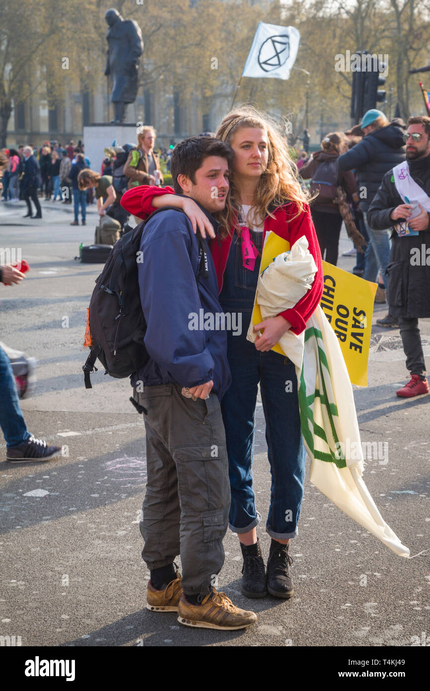 """A young couple with a """"Save our Children"""" banner by Parliament Square, Westminster for the Extinction Rebellion demonstration Stock Photo"""
