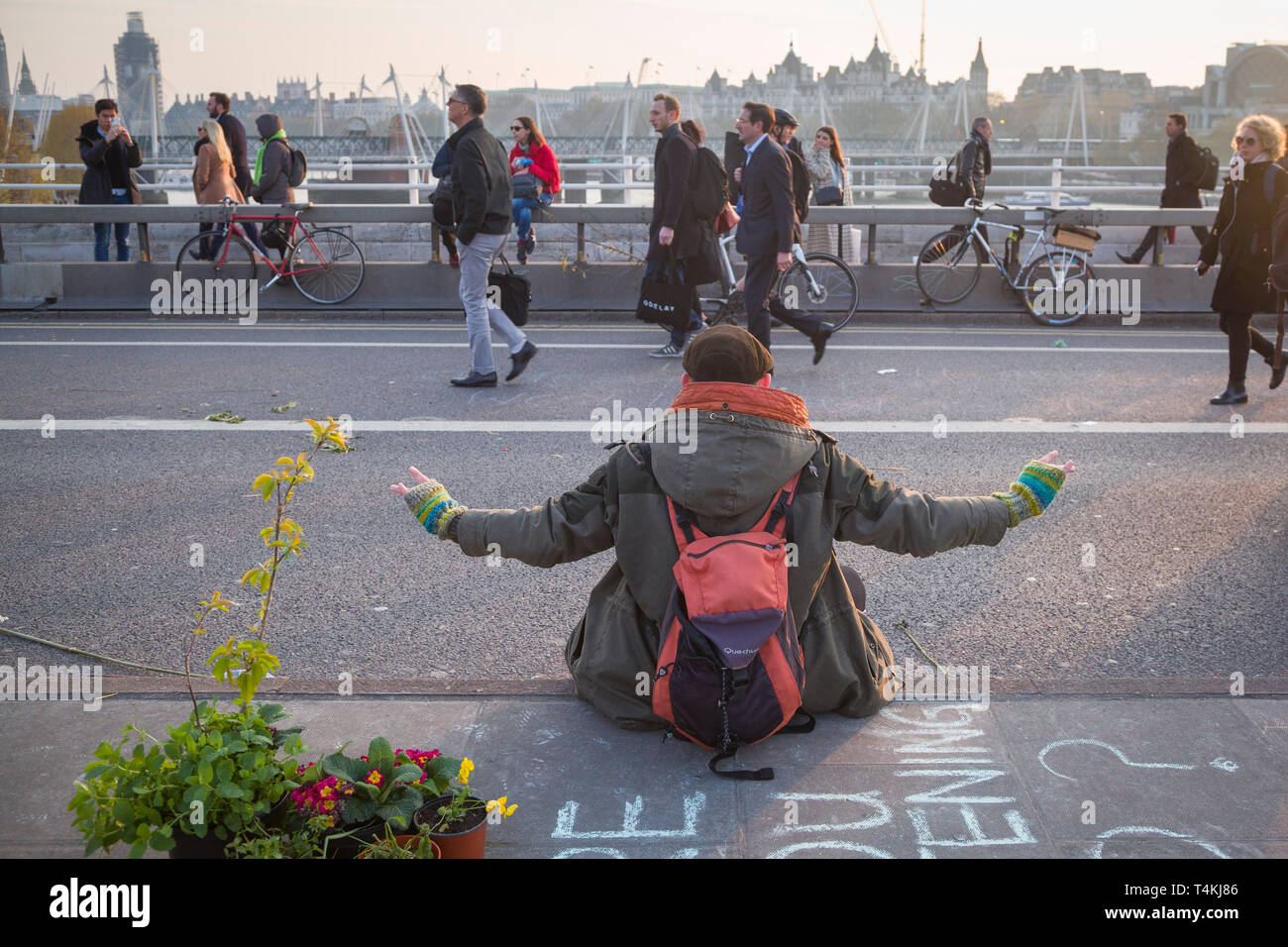 A demonstrator meditates on Waterloo Bridge for the Extinction Rebellion demonstration as people walk by Stock Photo