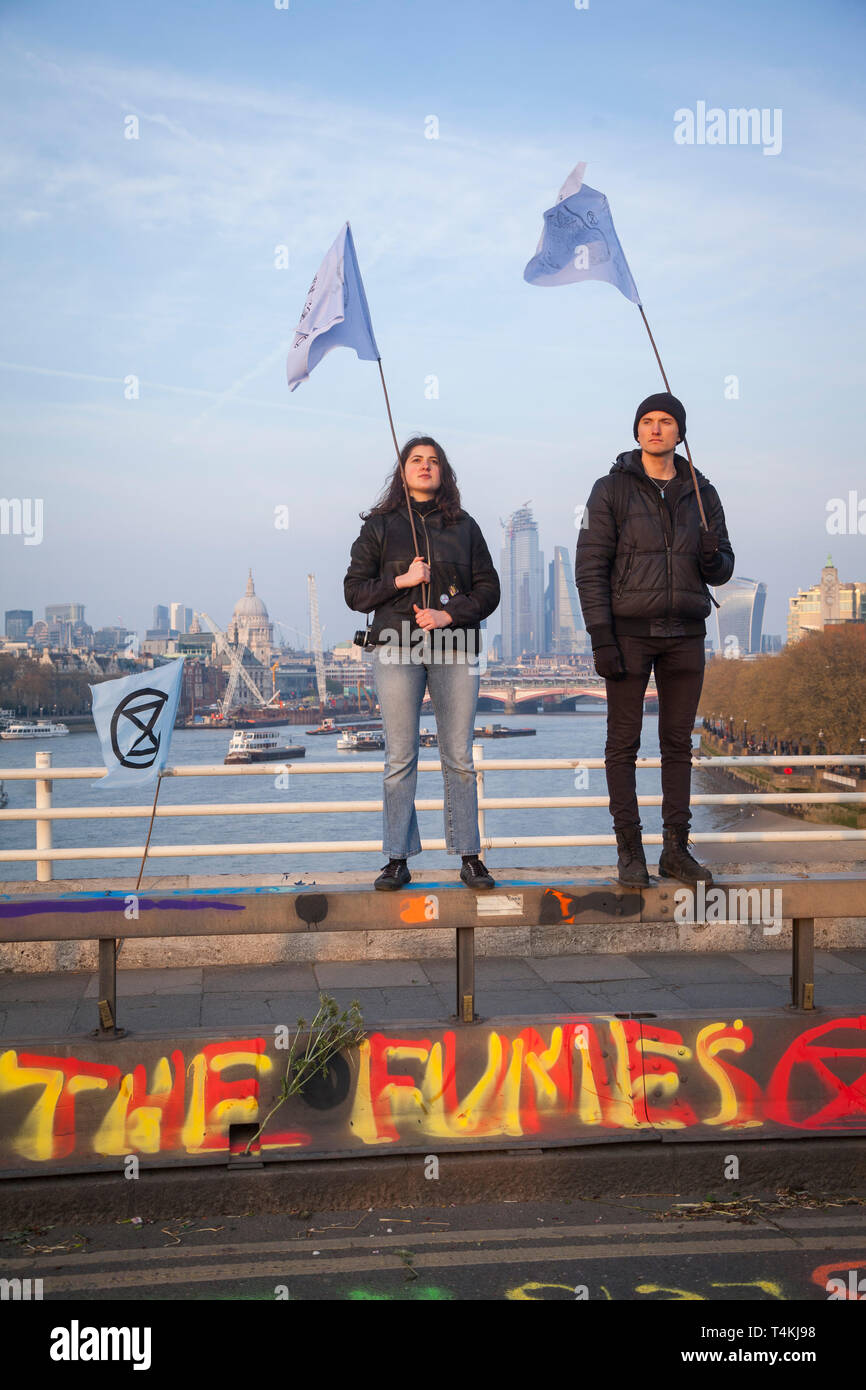 Two protestors stand holding flags on Waterloo Bridge for the Extinction Rebellion demonstration with the City of london behind Stock Photo