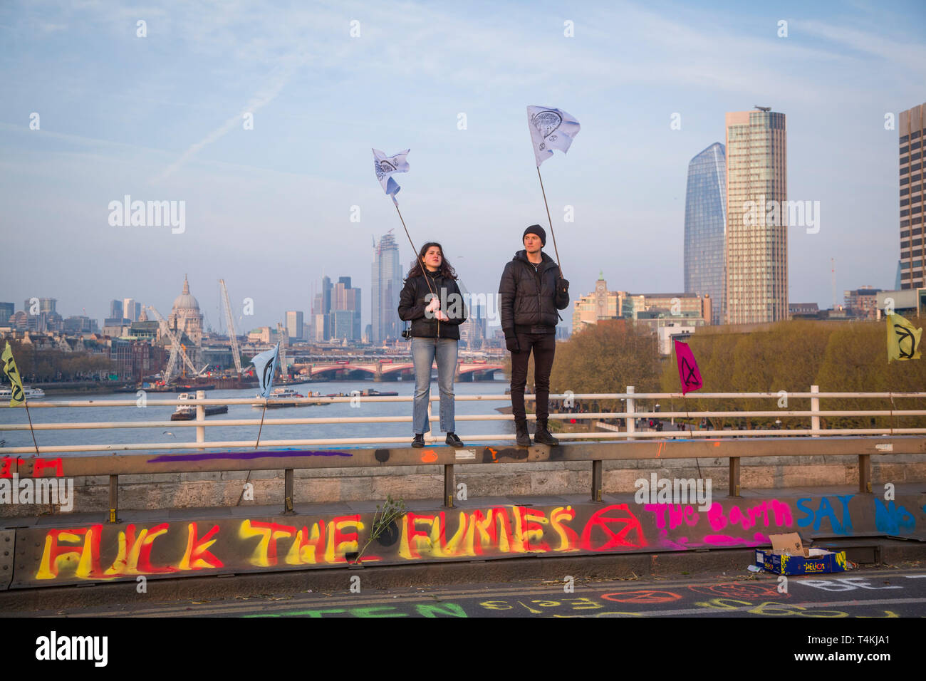 Two protestors stand holding flags on Waterloo Bridge for the Extinction Rebellion demonstration with the City of london behind - Stock Image