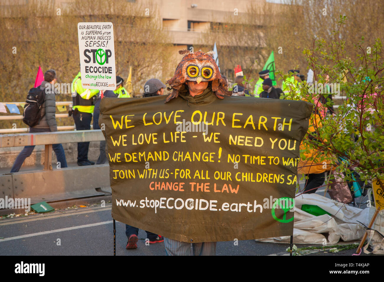 A protestor dressed as an owl holding a banner on Waterloo Bridge for the Extinction Rebellion demonstration Stock Photo