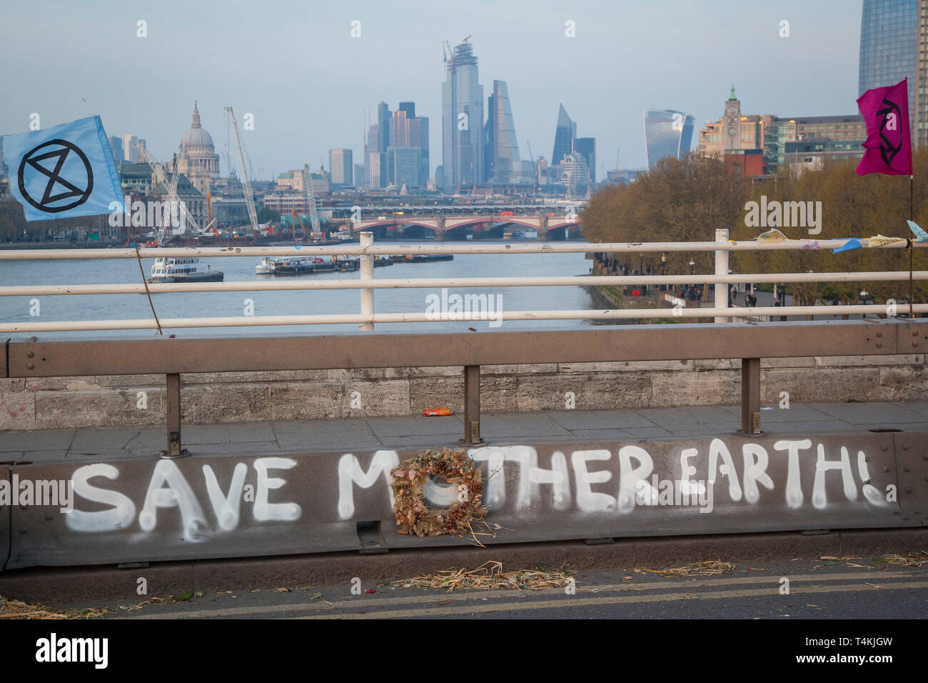"A ""Save Mother Earth"" banner painted on Waterloo Bridge for the Extinction Rebellion demonstration with hte City of london behind Stock Photo"