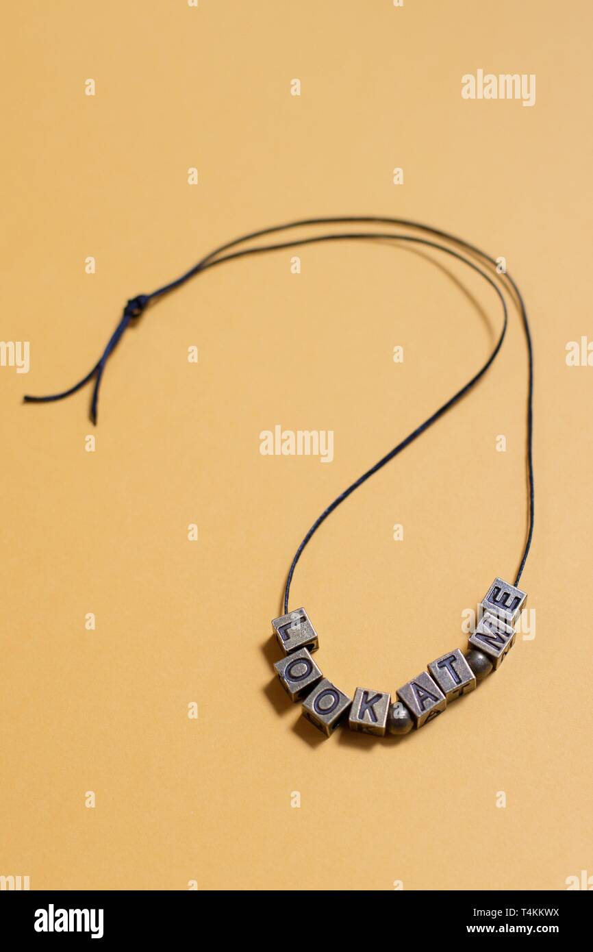 """The words """"look at me"""" spelled out by letter beads on a necklace. Stock Photo"""