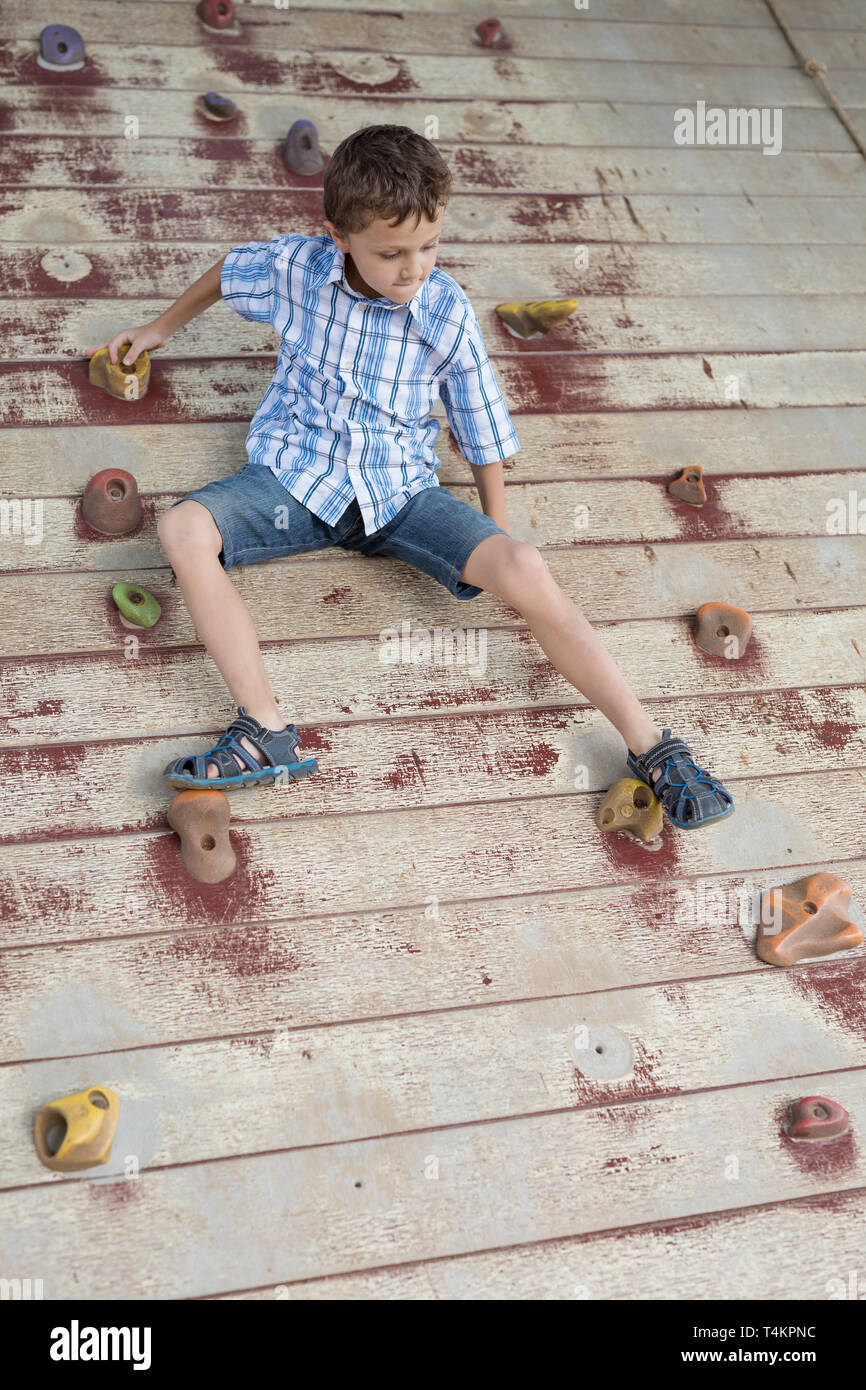 little boy climbing a rock wall outdoor. Concept of sport life. - Stock Image