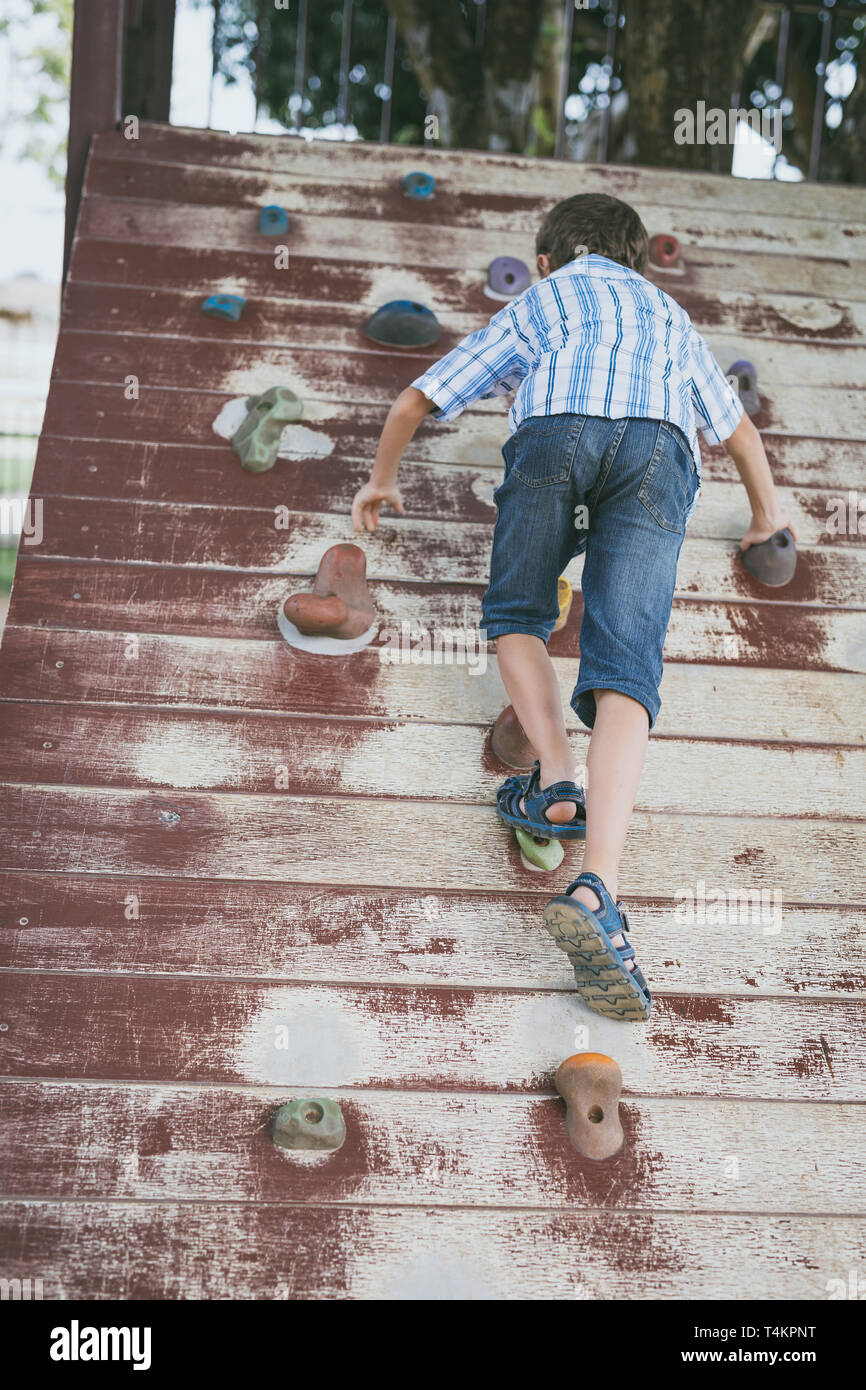 little boy climbing a rock wall indoor. Concept of sport life. - Stock Image