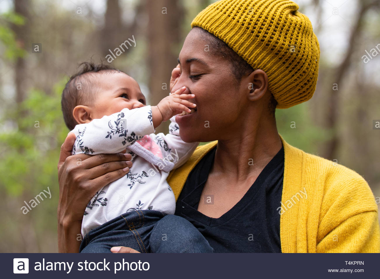 Baby playing with her mothers nose - Stock Image