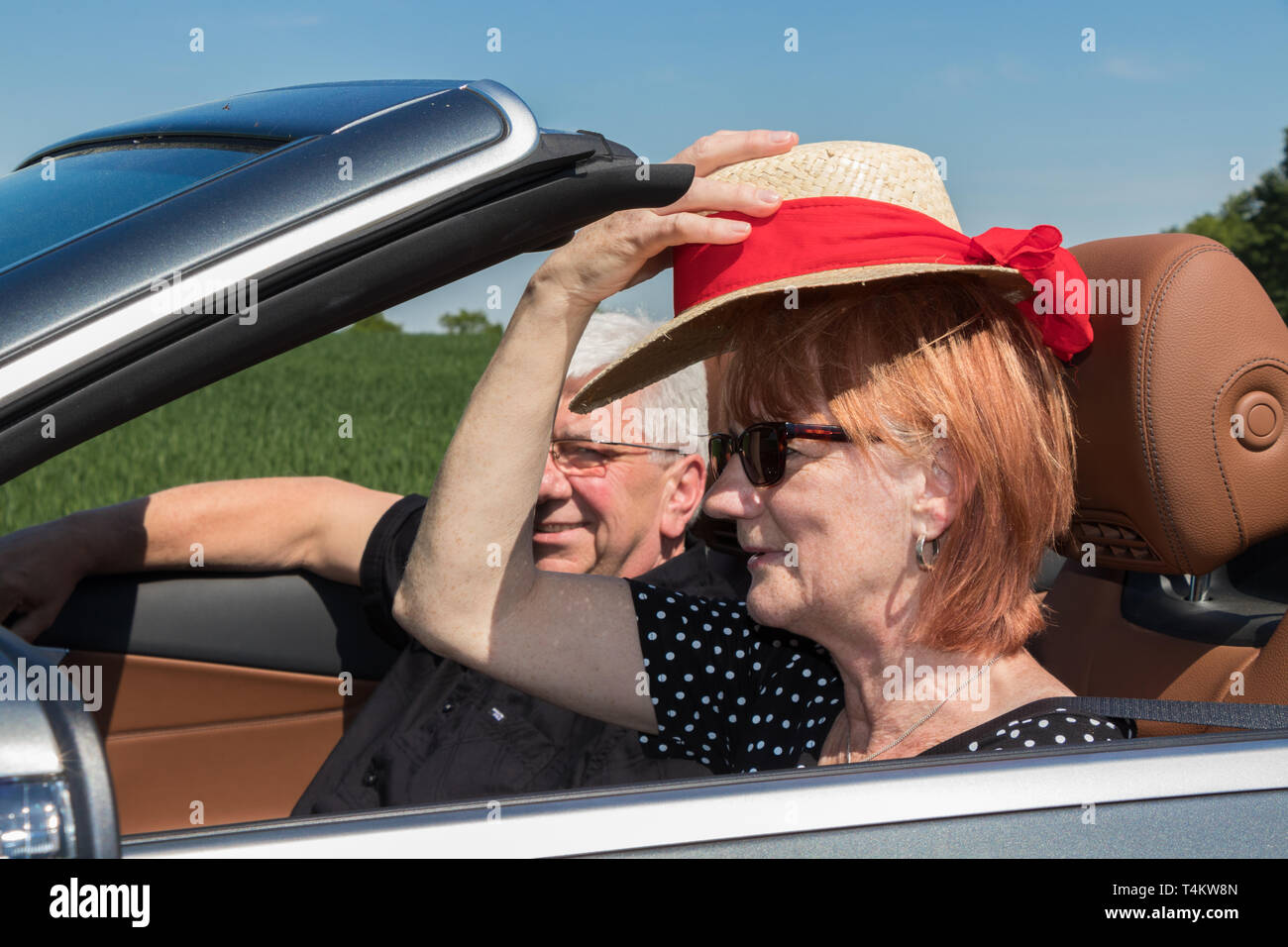 Beautiful older woman with partner in a luxury convertible car - Stock Image