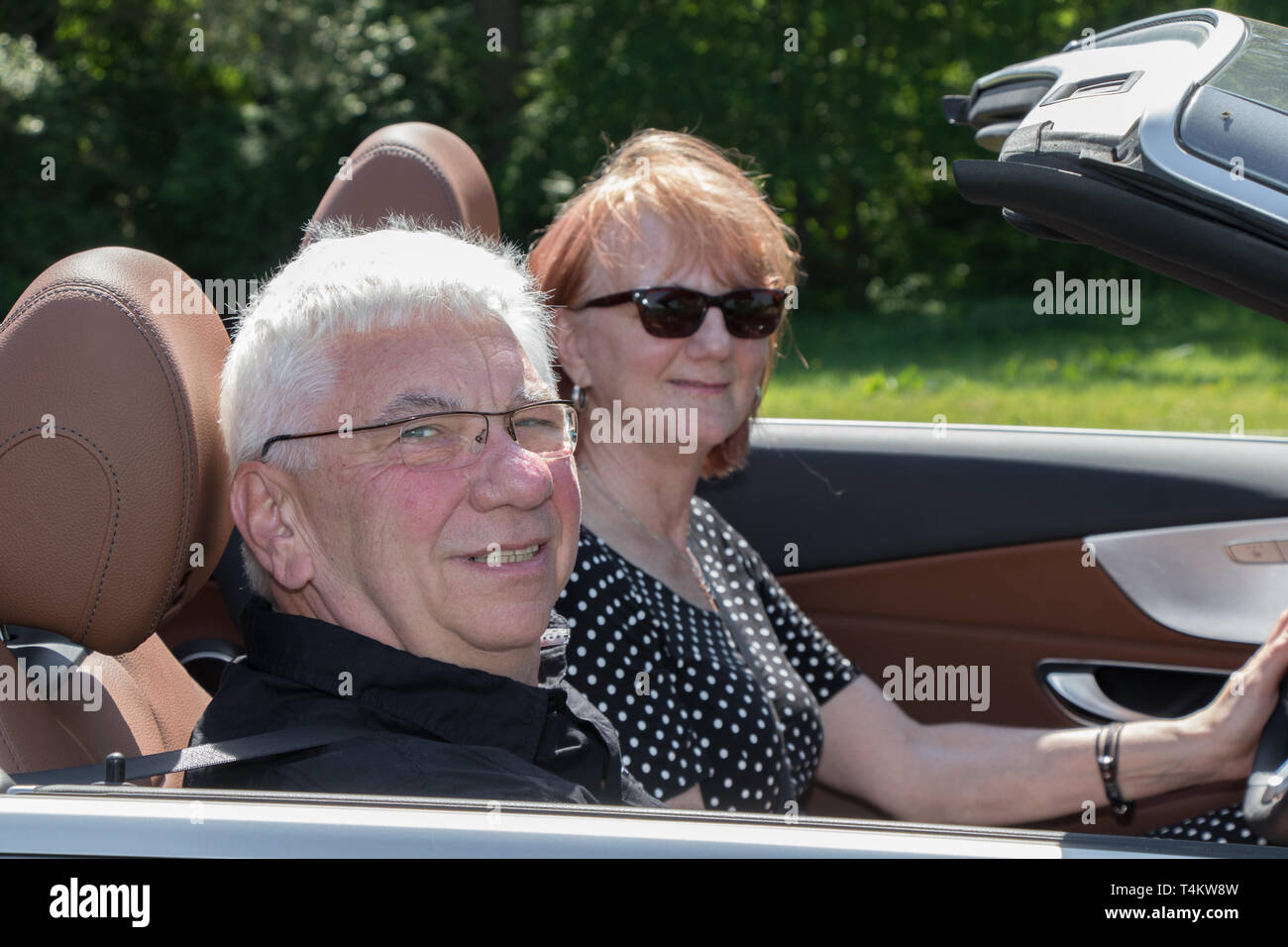 Happy older couple drives with a luxury convertible car on a sunny day - Stock Image
