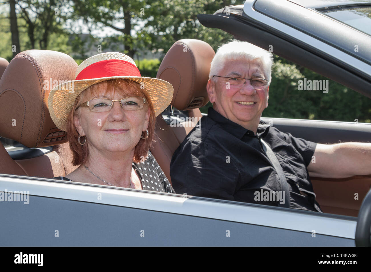 Older couple in a luxury convertible car on a sunny day - Stock Image
