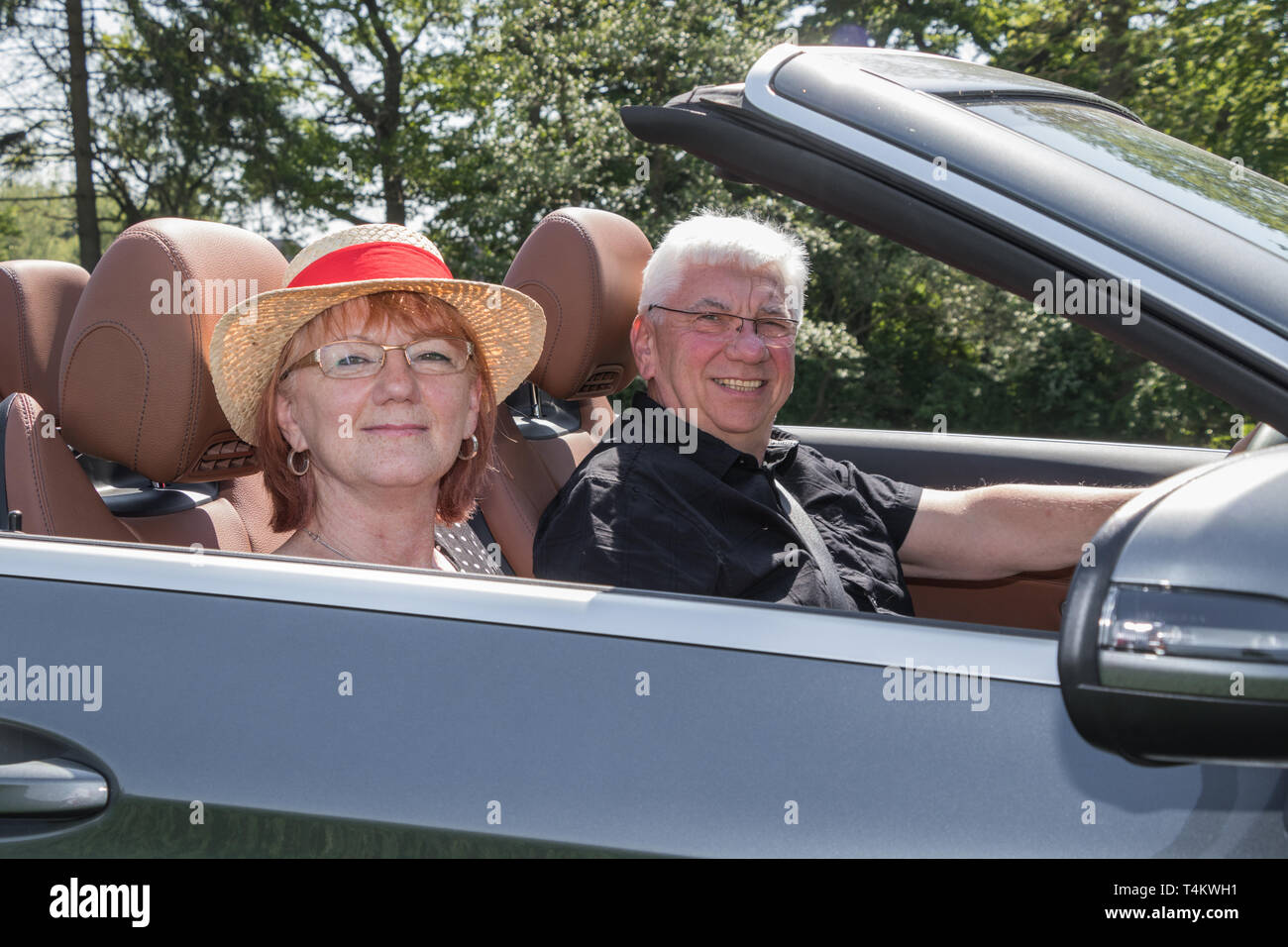 Older couple drives with a luxury convertible car - Stock Image