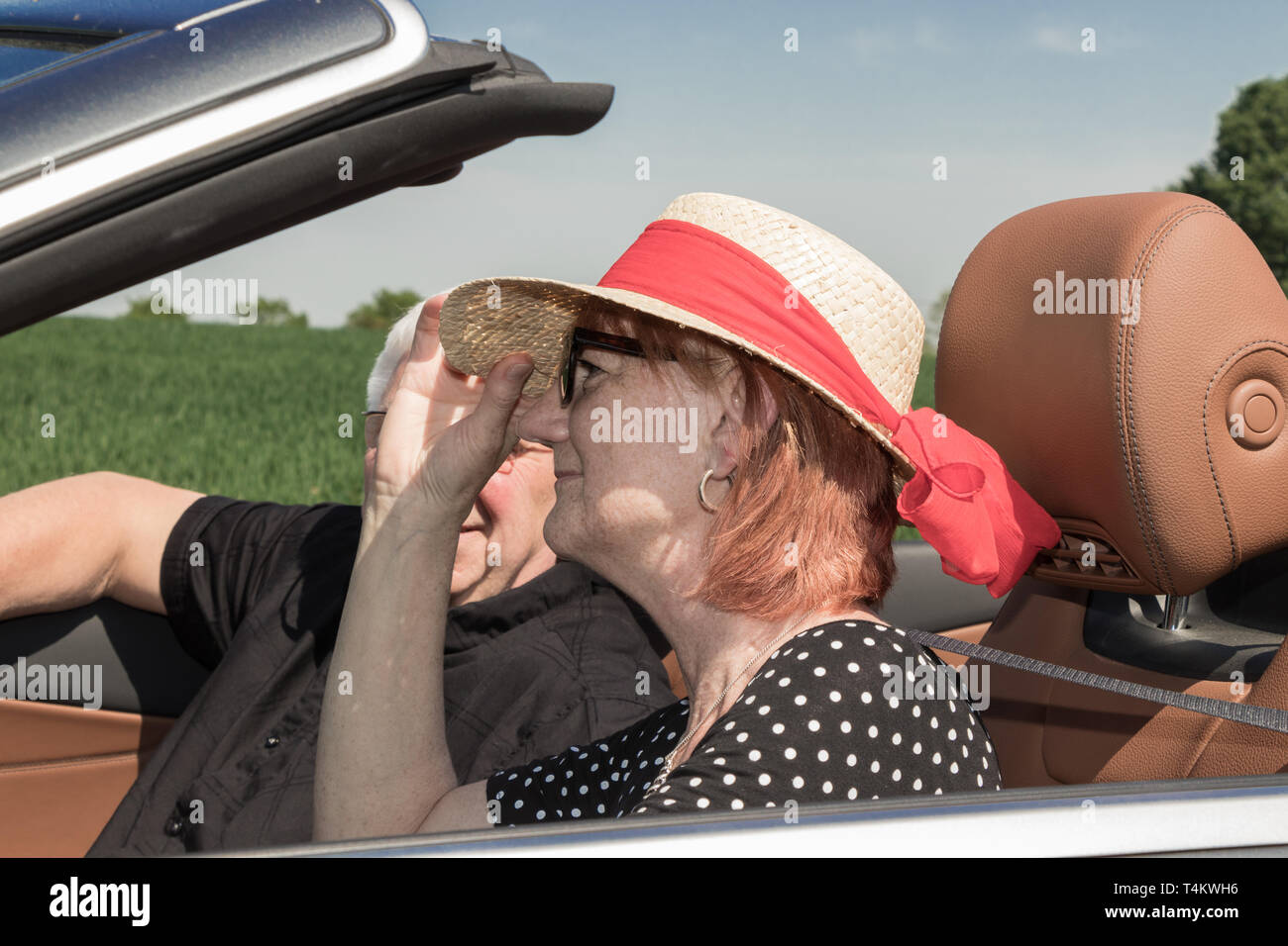 Happy older woman with a sun hat and her partner in a luxury convertible car - Stock Image