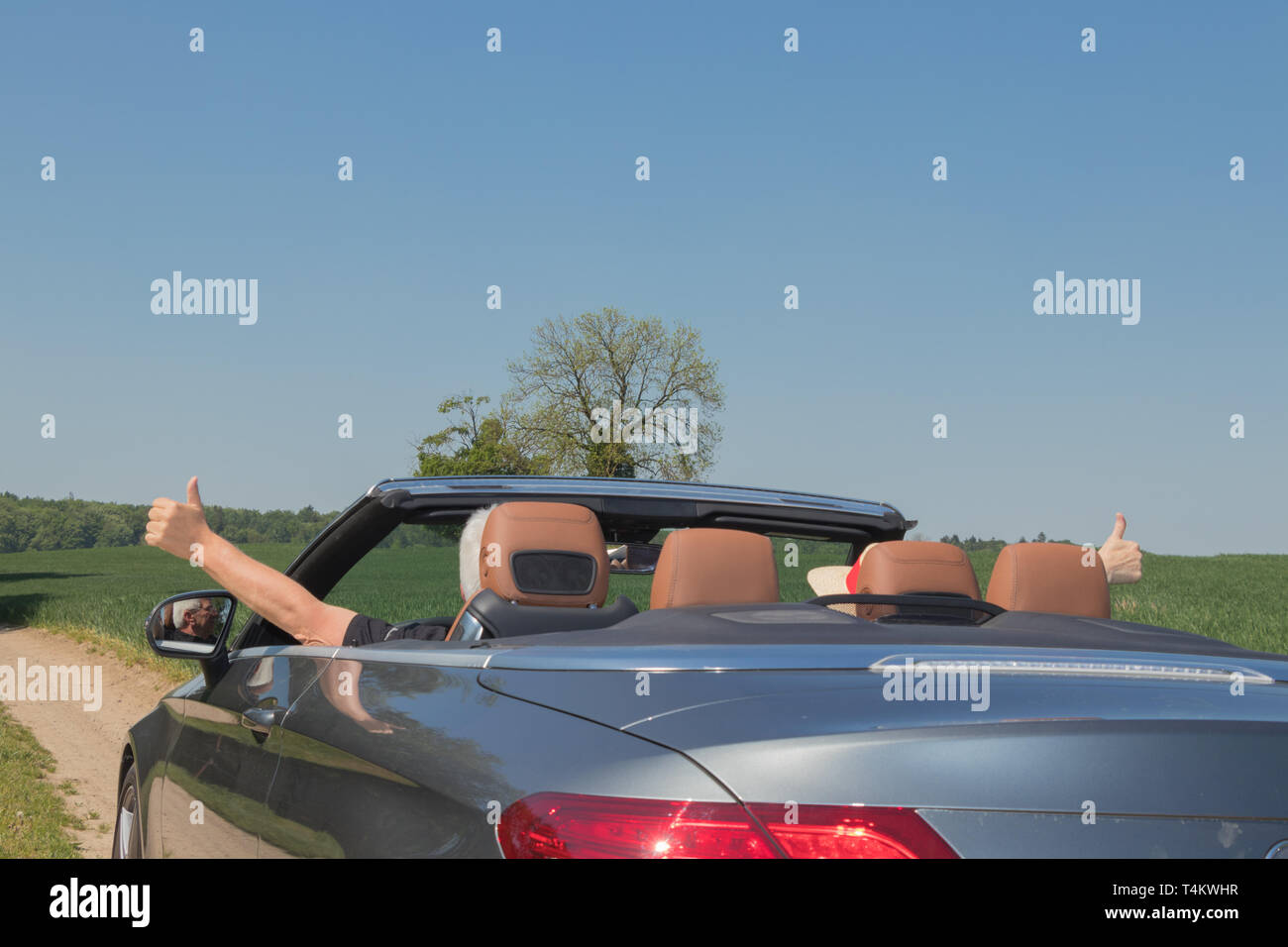 older couple drives with a luxury convertible car in the nature - Stock Image