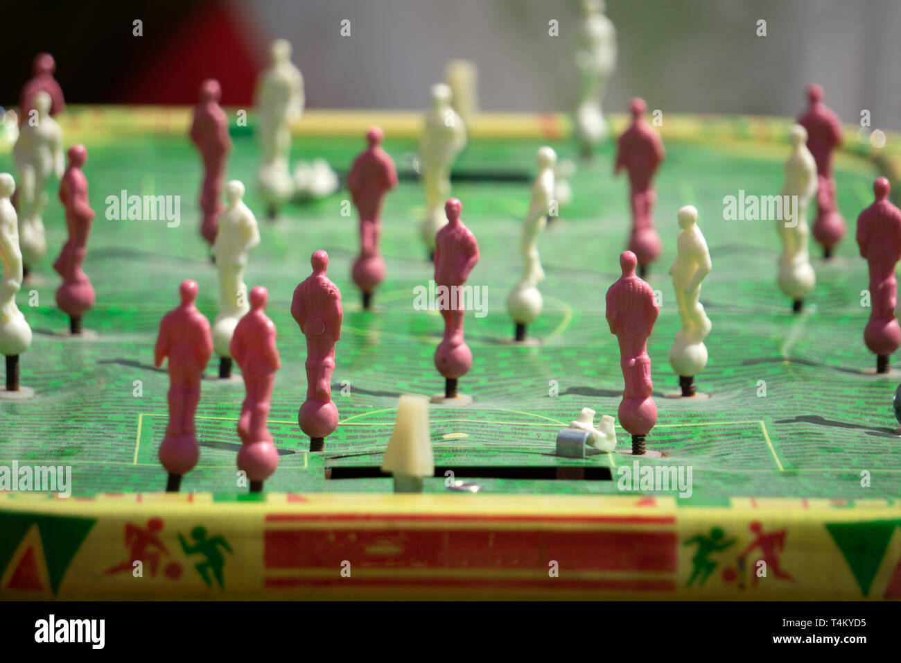 Detail of girl's hands playing the foosball vintage table match. Color toned image. Concept photo of leading the company. - Stock Image