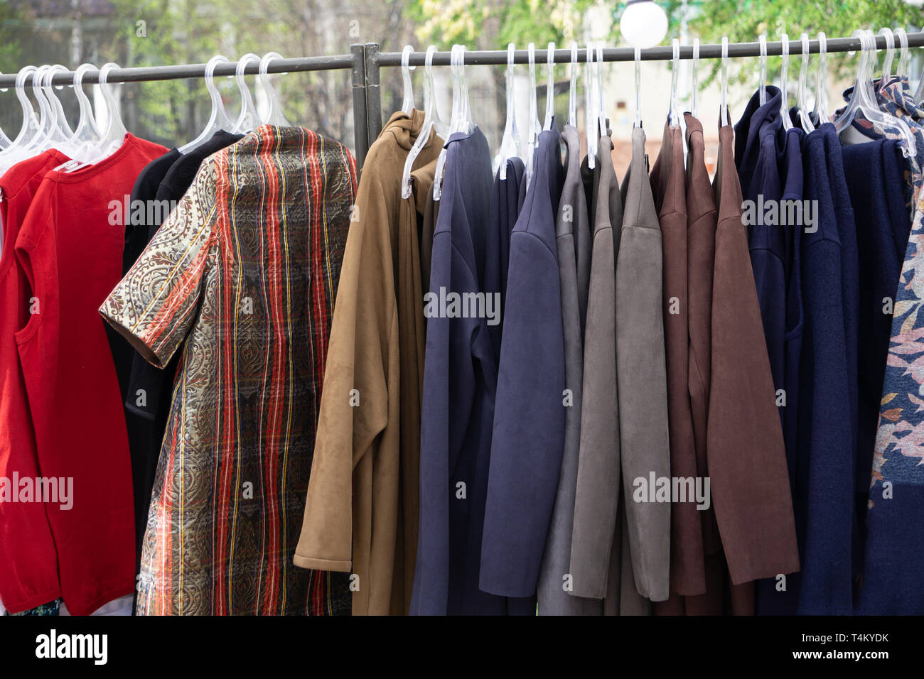 Variety of women's skirts on hangers at fashion clothing store in . - Stock Image