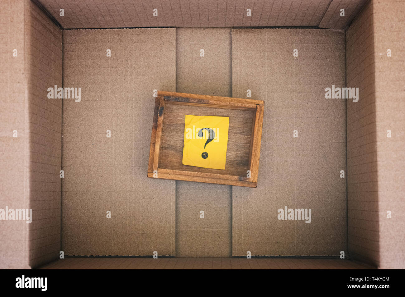 Wooden box with question mark inside cardboard box. Concept image. Close up. - Stock Image