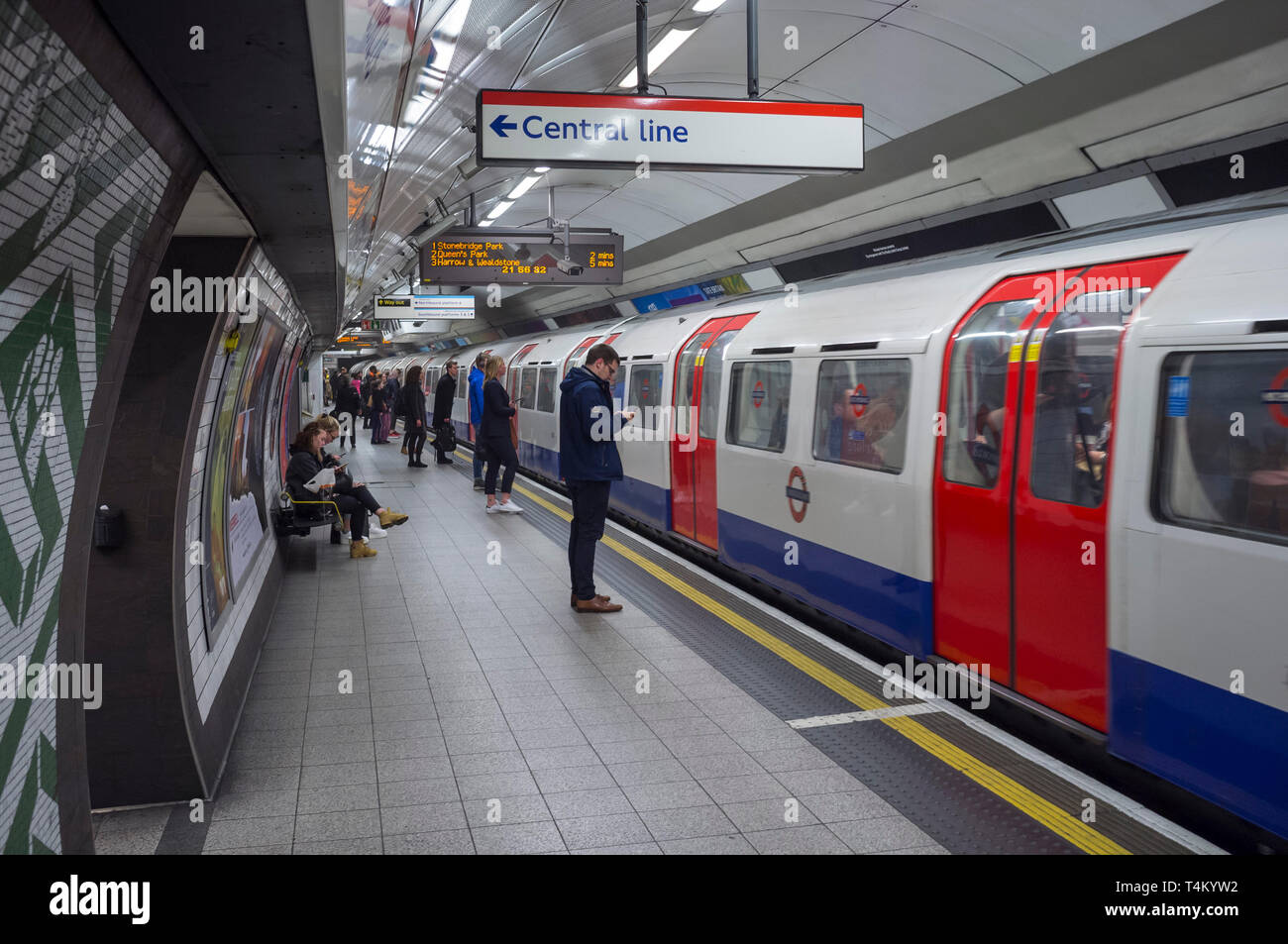 Commuters wait on the platform to get on to a Central Line tube at Waterloo Tube Station, London Stock Photo
