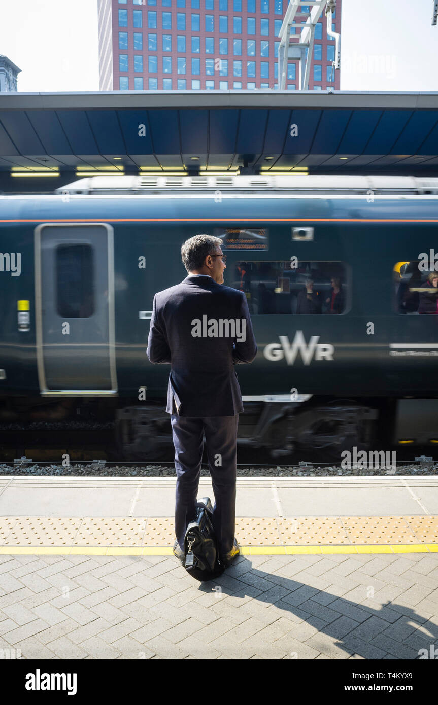 A commuter with a briefcase waits on the platform at Reading Station, Berkshire Stock Photo