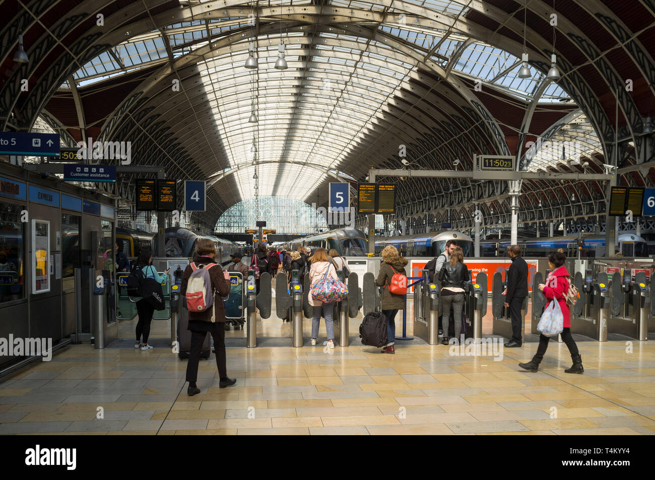 Travellers go through the turnstiles to their trains at Paddington Station, London - Stock Image