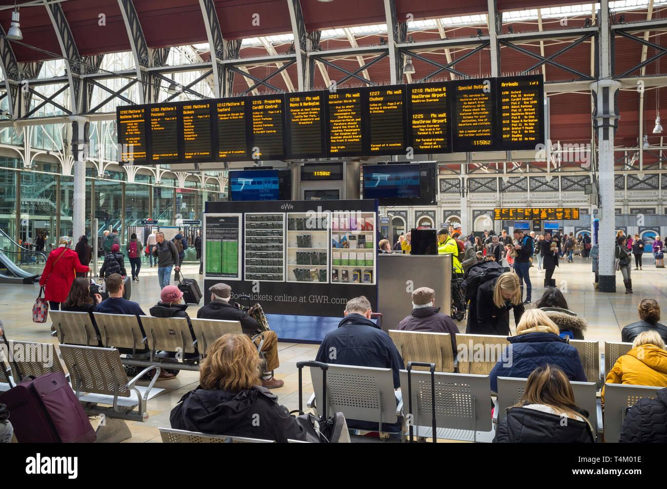 Travellers waiting by the illuminated display board at Paddington Station, london Stock Photo