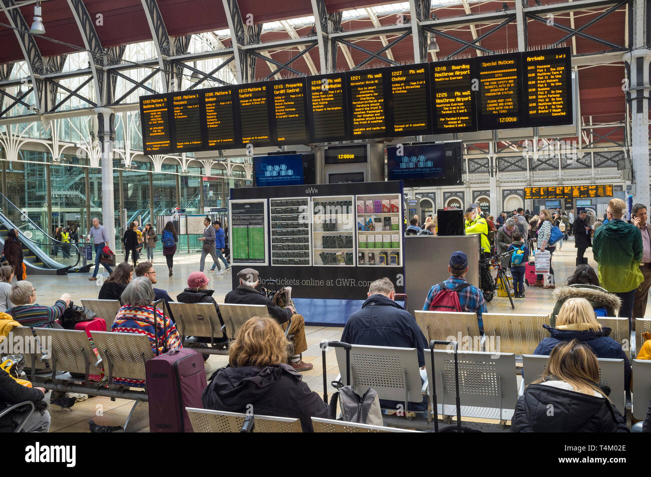 Travellers waiting by the illuminated display board at Paddington Station, london Stock Photo