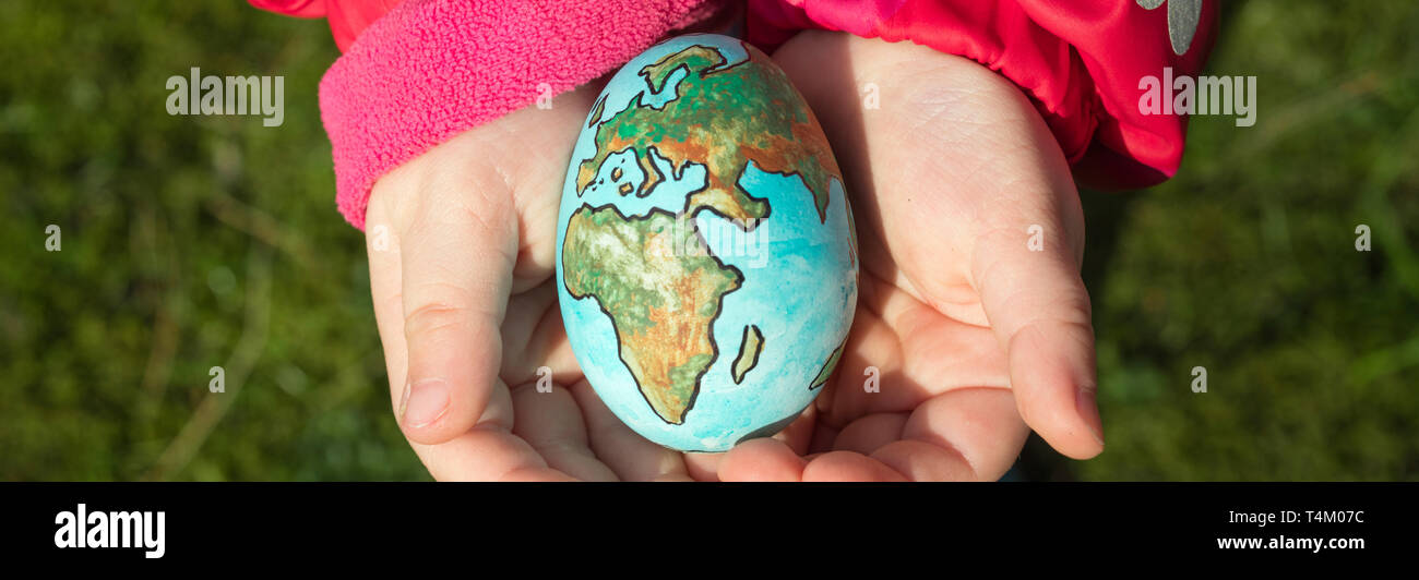 Child holding an egg with Planet Earth painted on it on a sunny day outdoors. - Stock Image