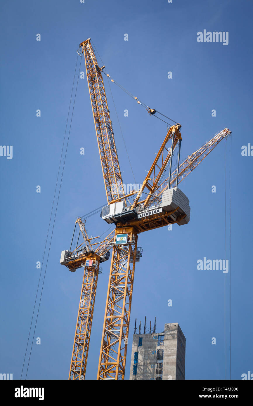 Two large Liebherr construction cranes against a clear blue sky - Stock Image