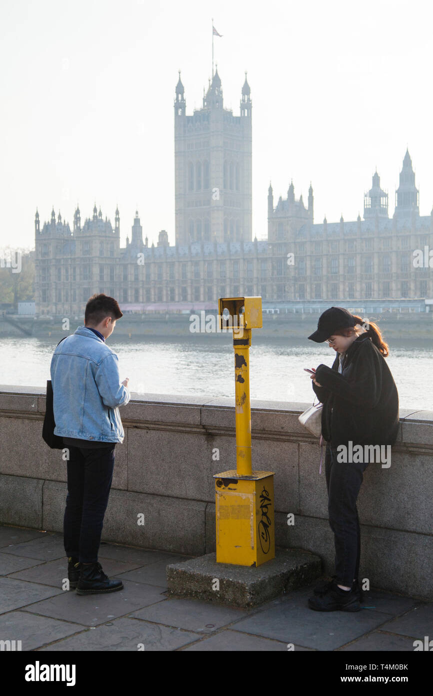 Two young foreign tourists look across to the Houses of Parliament over the River Thames - Stock Image
