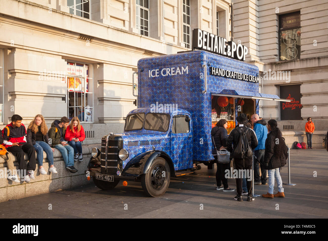 Tourists queue to buy hand-crafted ice-creams from a converted vintage Bedford ice cream van by Westminster Bridge, London - Stock Image