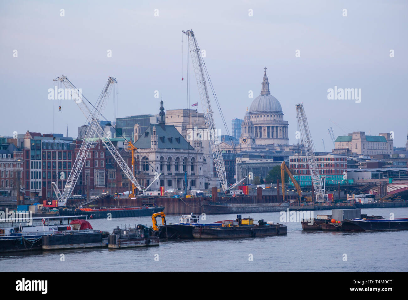 St. Paul's Cathedral in the evening light at dusk with cranes on the river - Stock Image